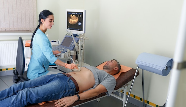 클리닉, 확대보기에서 남자의 복강 위의 초음파 진단. 의사는 환자의 남성 복부에 초음파 센서를 실행하고