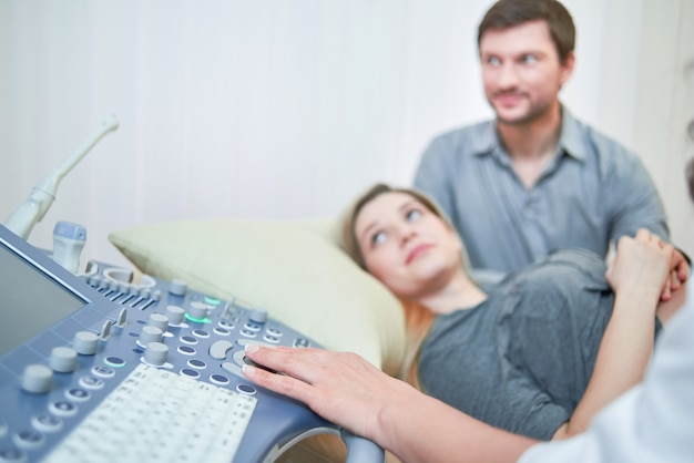 Ultrasound machine happy pregnant couple during ultrasound scanning procedure at the gynaecologist