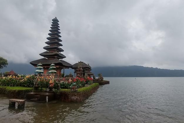 Ulun danu temple beratan lake in bali indonesia an mountain in fog near the water