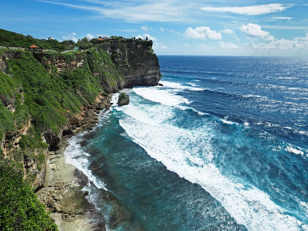 Uluwatu temple with ocean and cliff view with clear sky in bali, indonesia.