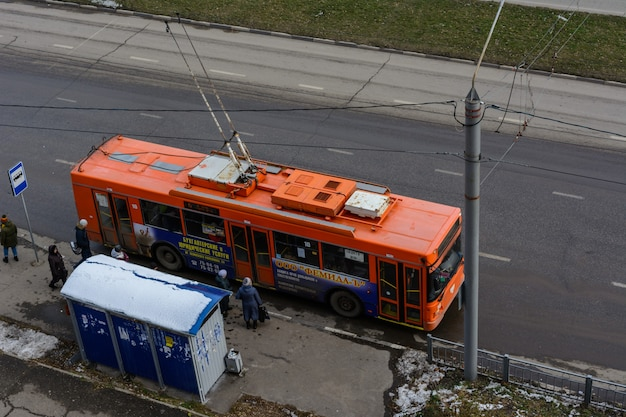 Ulyanovsk, russia - december 03, 2019: modern electric trolley bus departing from public transport stop in the winter sunny day. environmentally friendly transport.