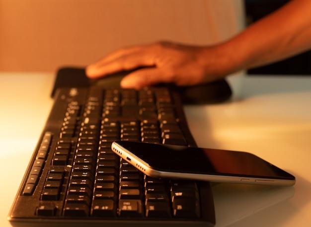Um celular sobre um teclado e uma pessoa segurando um mouse com uma luz quente