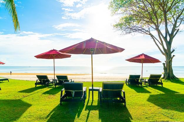 바다 해변 전망과 푸른 하늘이있는 우산과 비치 의자