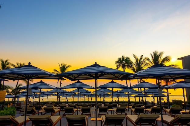 休日の休暇のためのホテルリゾートの屋外スイミングプールの周りの傘と椅子