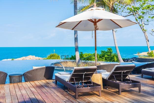 여행 휴가를위한 바다 바다 전망이있는 호텔 리조트의 야외 수영장 주변의 우산과 의자