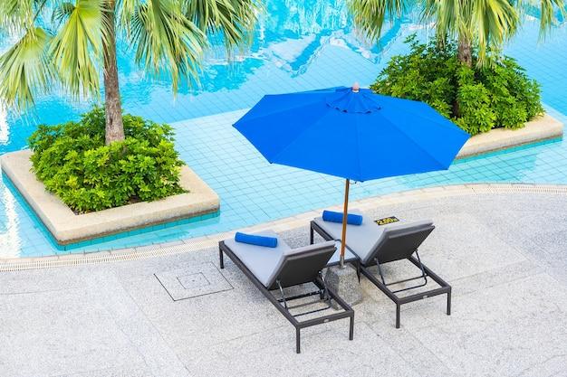 ホテルリゾートの屋外スイミングプールの周りの傘と椅子