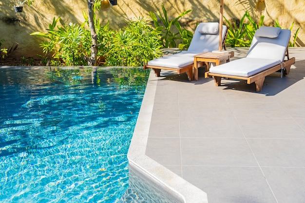 휴가 레저를위한 리조트 호텔의 야외 수영장 주변 우산과 의자