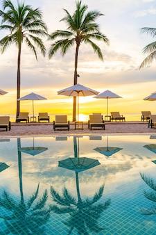 Зонтик и кресло вокруг бассейна в курортном отеле с восходом солнца утром - концепция отпуска и отпуска