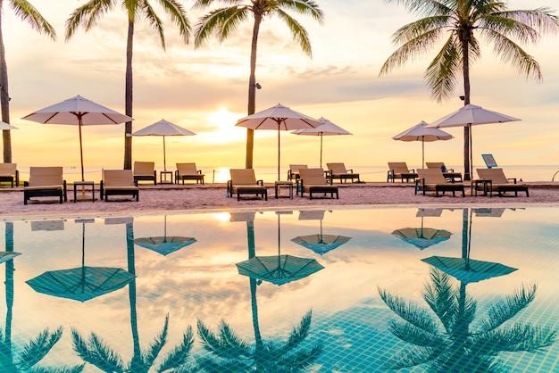 아침에 일출과 호텔 리조트 수영장 주변의 우산과 의자. 휴가 및 휴가 개념