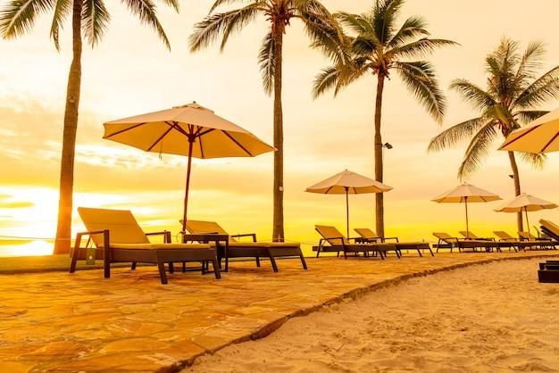 아침에 일출이 있는 호텔 리조트 수영장 주변의 우산과 의자 - 휴일 및 휴가 개념