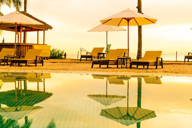 朝の日の出とホテルリゾートのスイミングプールの周りの傘と椅子-休日と休暇のコンセプト