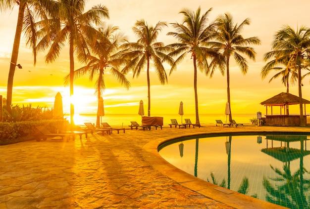 아침에 일출과 호텔 리조트 수영장 주위 우산과 의자
