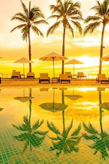 Зонтик и кресло вокруг бассейна в курортном отеле с восходом солнца утром