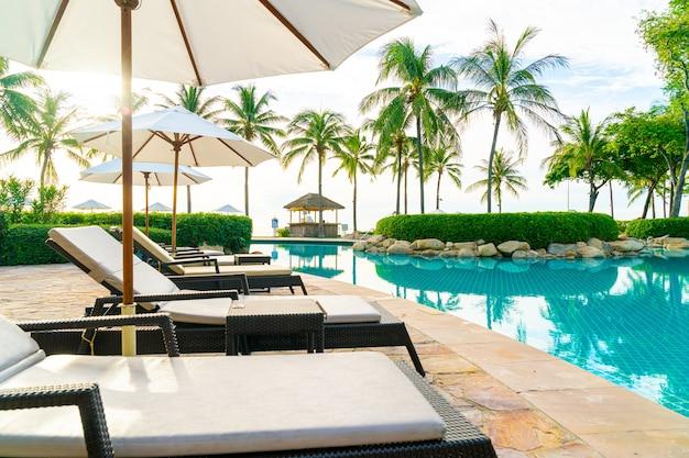海の海のビーチの近くのレジャー旅行や休暇のためのリゾートホテルのプールの周りの傘と椅子