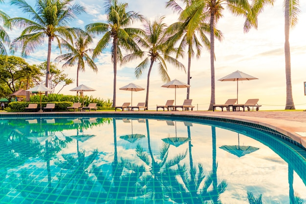 日没または日の出の時間にレジャー旅行や休暇の近くの海の海のビーチのためのリゾートホテルのプールの周りの傘と椅子