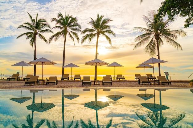 Зонтик и кресло вокруг бассейна в курортном отеле для путешествий и отдыха рядом с пляжем у моря и океана на закате или восходе солнца
