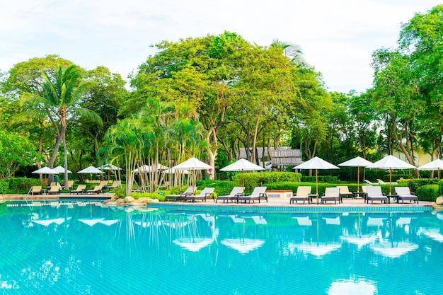 레저 여행 및 휴가를위한 리조트 호텔 수영장 주변의 우산과 의자 일몰 또는 일출 시간에 가까운 바다 바다 해변