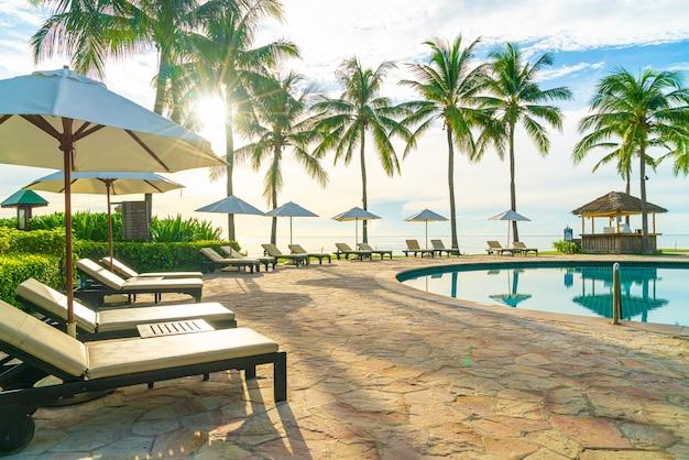 일몰 또는 일출 시간에 바다 해변 근처에서 레저 여행 및 휴가를 즐길 수 있는 리조트 호텔 수영장 주변의 우산과 의자