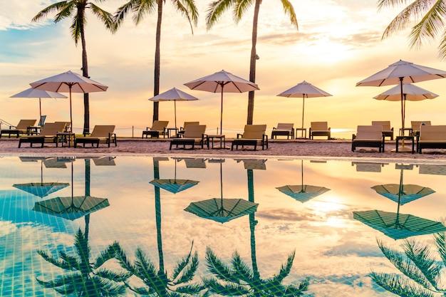 レジャー旅行や休暇の近くの海の海のビーチのためのリゾートホテルのプールの周りの傘と椅子