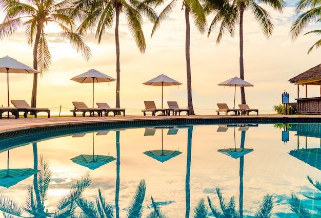 レジャー旅行や休暇の近くの海のためのリゾートホテルのプールの周りの傘と椅子