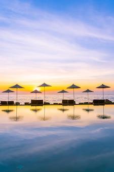 레저 여행 및 휴가를위한 리조트 호텔의 수영장 주변 우산과 의자