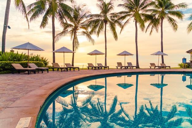 海の海のビーチの近くの休暇のためのリゾートホテルのプールの周りの傘と椅子