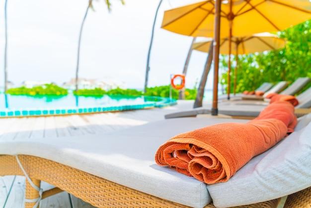 Зонтик и кресло вокруг бассейна в курортном отеле