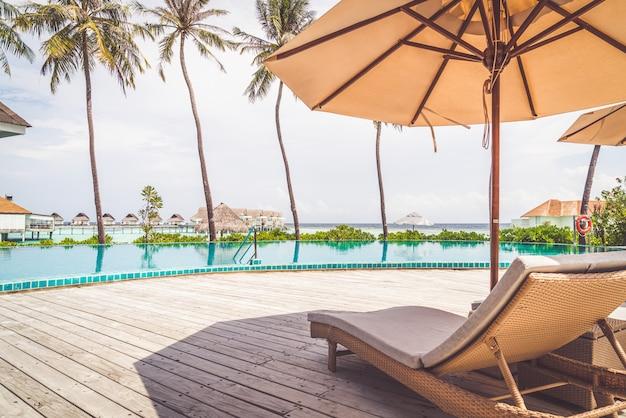 リゾートホテルのスイミングプールの周りの傘と椅子