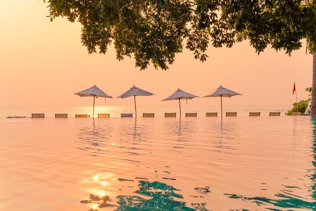 休日の休暇旅行のコンセプトのための海の海の景色を望むスイミングプールの周りの傘と椅子