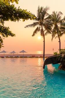 휴가 휴가 여행 개념에 대한 바다 바다 전망이있는 수영장 주변의 우산과 의자