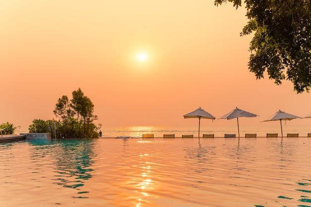 休日の休暇旅行の概念のための海の海の景色を望むスイミングプールの周りの傘と椅子