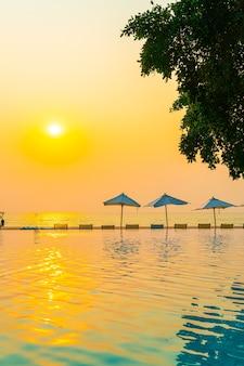 海の海の景色を望むスイミングプールの周りの傘と椅子