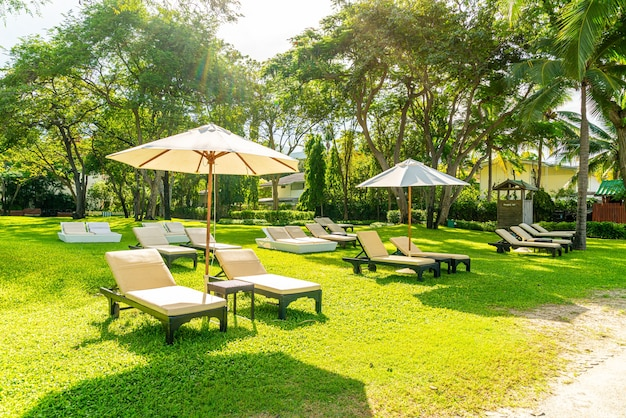 Зонтик и стул в саду для принятия солнечных ванн или отдыха