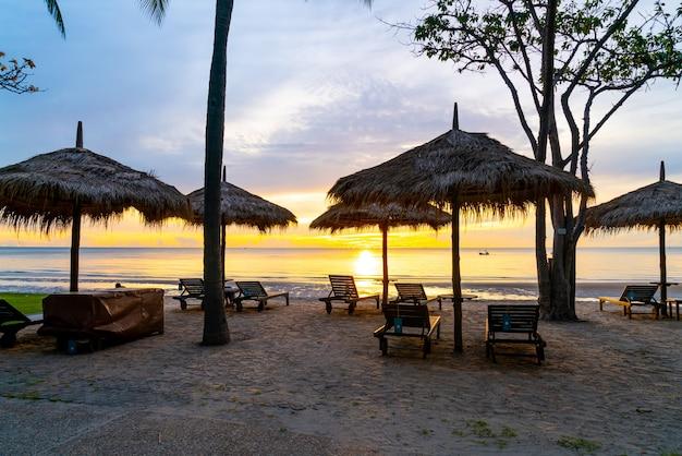 아침에 일출과 열 대 해변에 우산과 의자