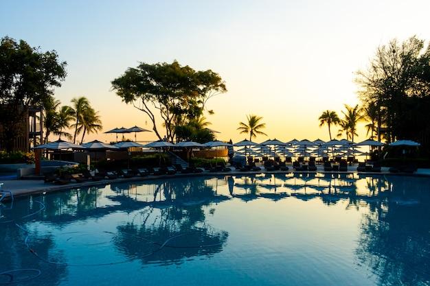 일몰 또는 일출 하늘과 휴가 휴가를 위해 호텔 리조트의 야외 수영장 주변에 우산과 의자 소파