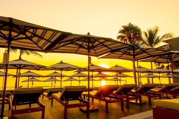 日没または日の出の空との旅行休暇休暇のためのホテルリゾートの屋外スイミングプールの周りの傘と椅子のソファ