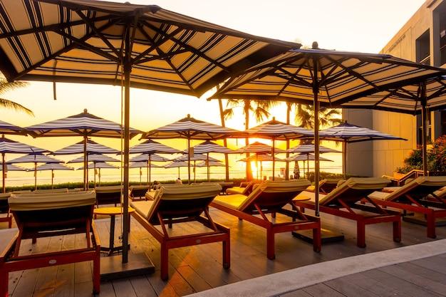 일몰 또는 일출 하늘과 여행 휴가 휴가를 위해 호텔 리조트의 야외 수영장 주변에 우산과 의자 소파