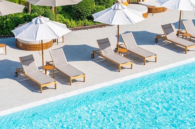 ホテルリゾートのほぼ海のビーチの海の屋外スイミングプールの周りの傘とデッキチェア