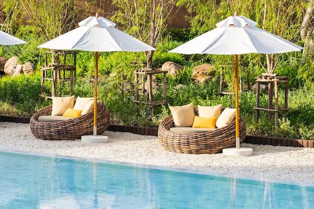 바다 바다 해변과 코코넛 야자 나무가있는 호텔 리조트의 야외 수영장 주변의 우산과 갑판 의자