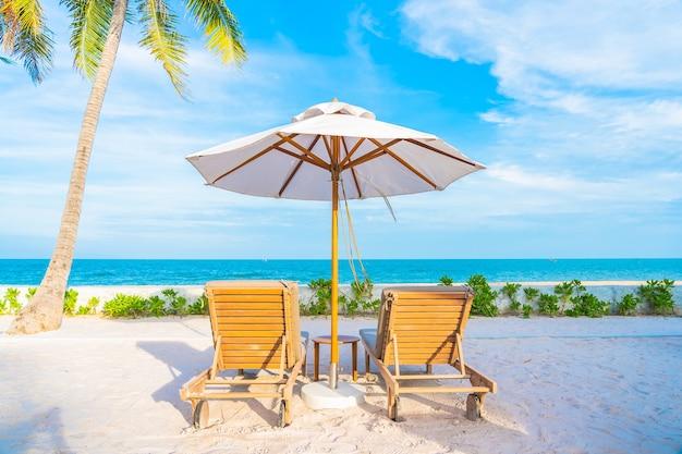 Зонтик и шезлонг вокруг открытого бассейна в курортном отеле с пляжем на берегу океана и кокосовой пальмой