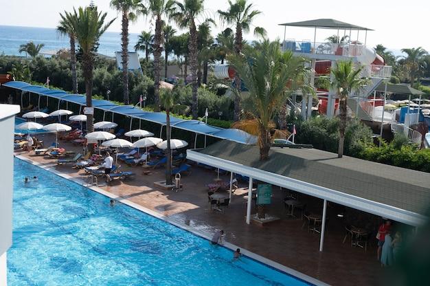 Зонтик и кровать у бассейна вокруг открытого бассейна в курортном отеле для путешествий, отдыха, отпуска. фото высокого качества