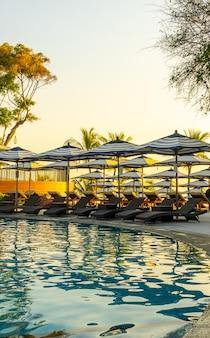 여행 휴가 휴가 개념에 대한 호텔 리조트의 야외 수영장 주변의 우산과 수영장 침대
