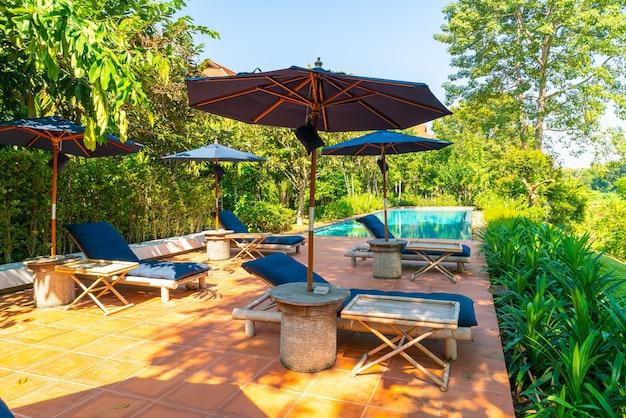 Зонтик и кровать вокруг бассейна с видом на реку