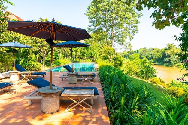 川の景色を望むスイミングプールの周りの傘とプールベッド