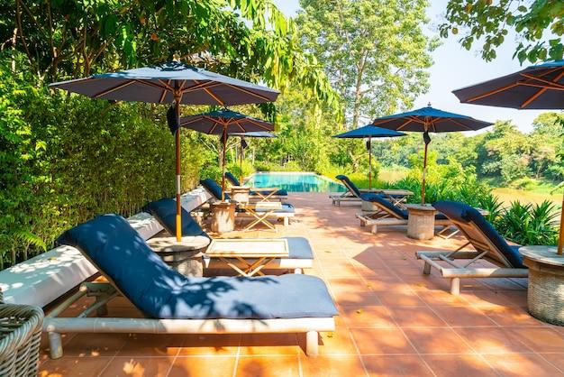 강이 보이는 수영장 주변의 우산과 수영장 침대