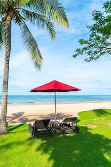 우산과 해변에서 야자수 아래 sunbed