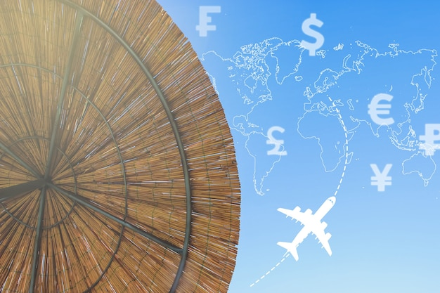 The umbrella of bambooblur background with currency icons different countries, the silhouette of world map, plane and morning sun . concept travel.