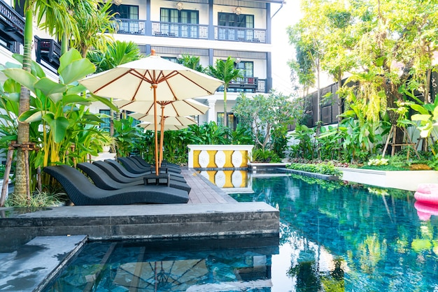 Umbrella and bed pool chair around swimming pool - vacation and travel holiday concept