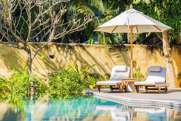 Ombrellone e sedia intorno alla piscina all'aperto in hotel resort per il tempo libero delle vacanze