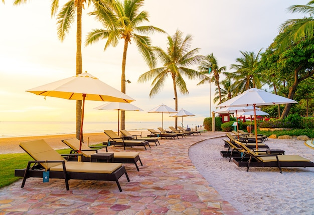 Umbrella and chair around swimming pool in hotel resort with sunrise in morning - holiday and vacation concept